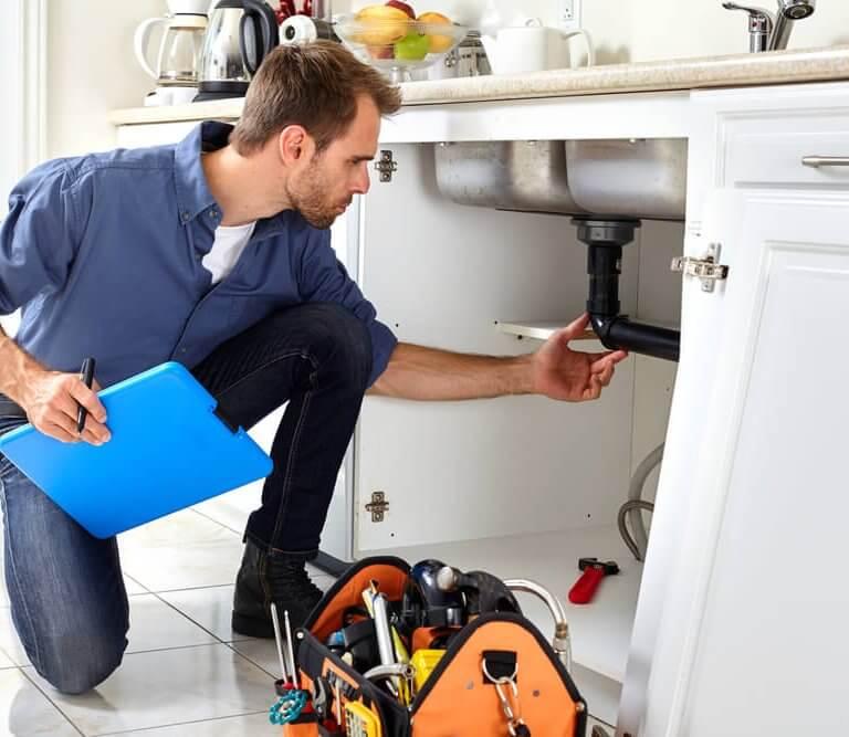 Man looking at plumbing under sink